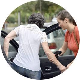 Femme aidant une personne âgée à rentrer dans une voiture