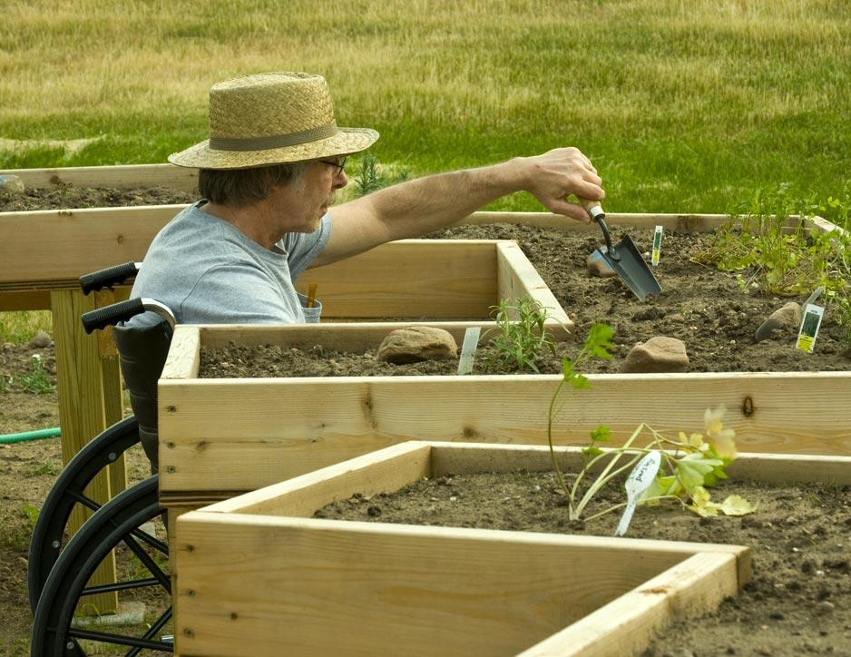 Personne en fauteuil roulant en train de jardiner