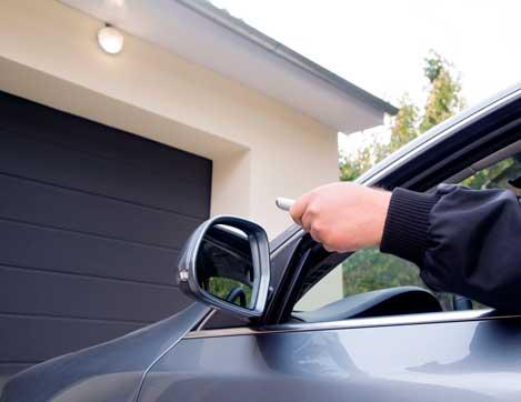 Personne en voiture qui ouvre son garage à l'aide d'une télécommande