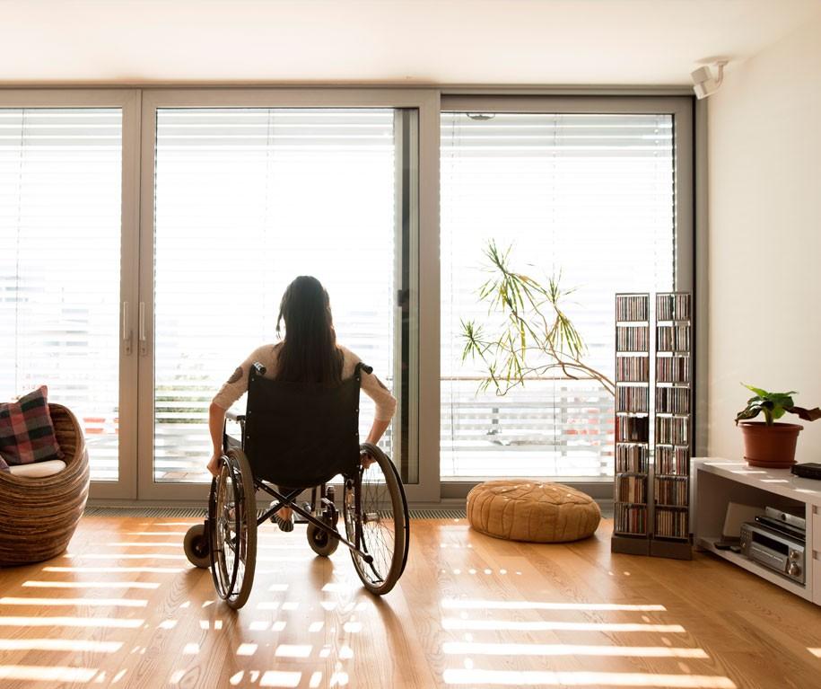 Femme dans un fauteuil roulant devant une porte-fenêtre avec volets roulants