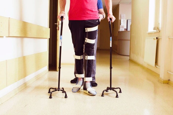 Personne avec orthèse qui marche dans le couloir d'un centre de rééducation