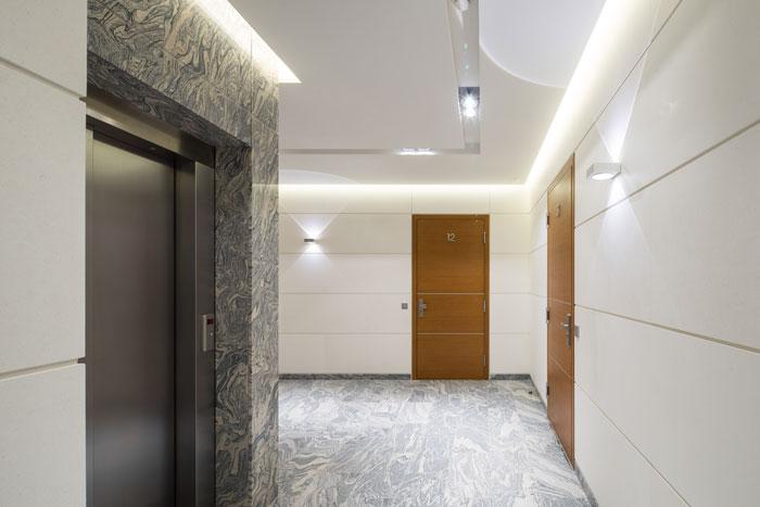 Hall d'immeuble avec ascenseur et portes larges